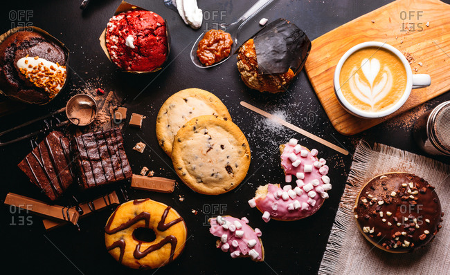 Flat lay of various doughnuts with sweet toppings and chocolate bars composed with cup of cappuccino on black table