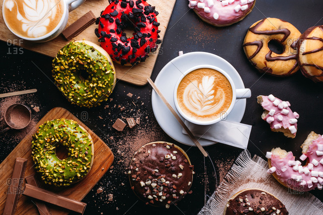 Various doughnuts with sweet toppings and chocolate bars composed with cup of cappuccino on black table