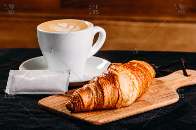 Golden crispy croissant served on wooden board with white cup of fresh coffee on black surface