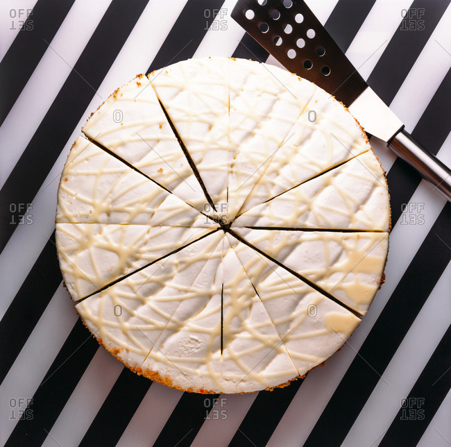 Top view of round cake with white cream and glaze cut in pieces for serving placed on black and white striped surface