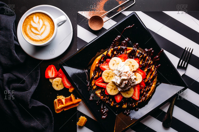 Top view of cappuccino in white mug on table with plate of round waffle with banana and strawberry topped with chocolate sauce and whipped cream