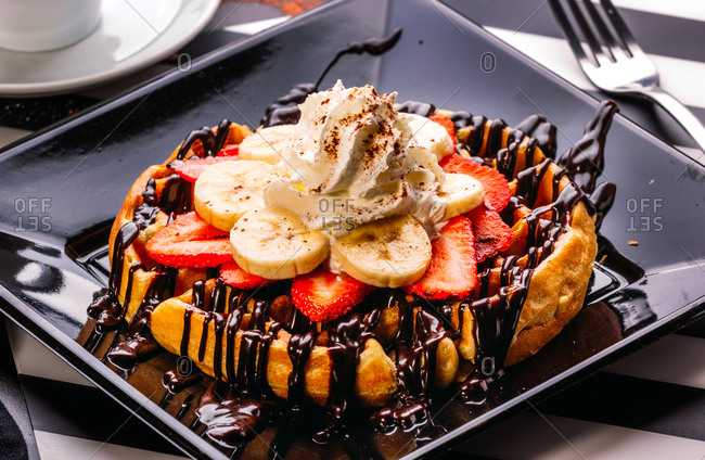 From above plate with round waffle with banana and strawberry topped with chocolate sauce and whipped cream