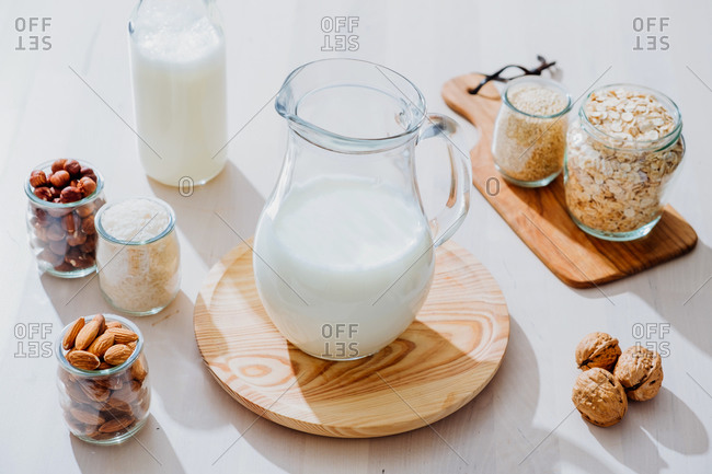 From above composition of glass jars with healthy vegan milk placed on table with various nuts and cereals
