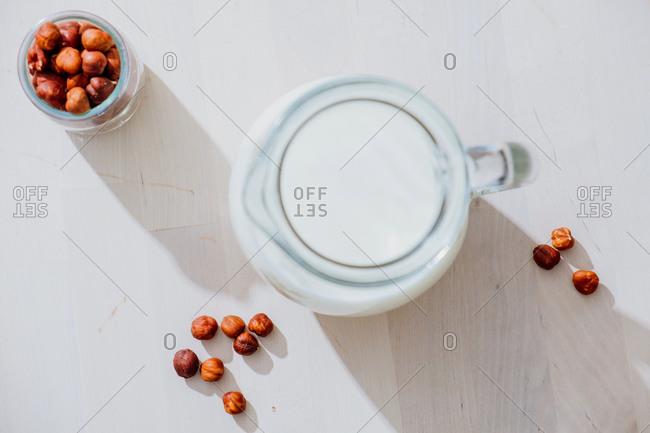 Jar of milk and hazelnuts on table