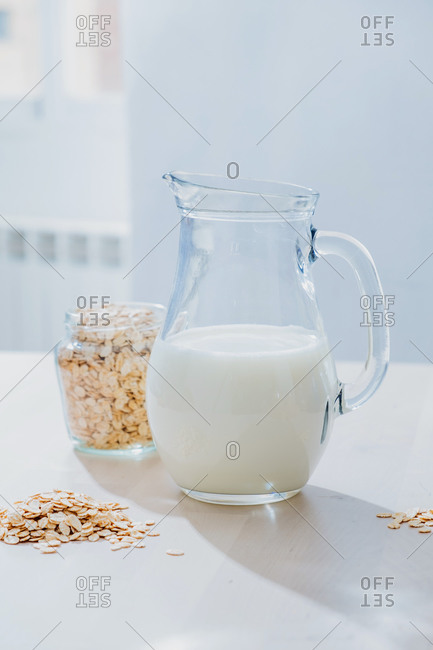 Jar of milk and oatmeal flakes on table