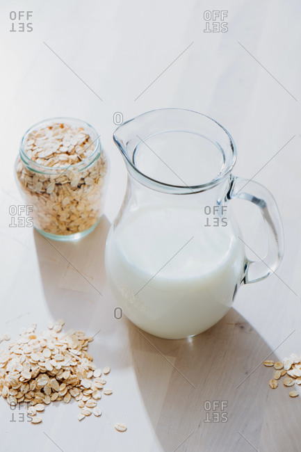 From above of glass jar with healthy vegan oat milk placed on wooden table with pot of oatmeal flakes