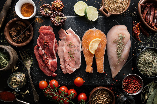 Top view of fillet of beef and pork with chicken and fish on black wooden cutting board in composition with different aromatic spices and seasonings on table