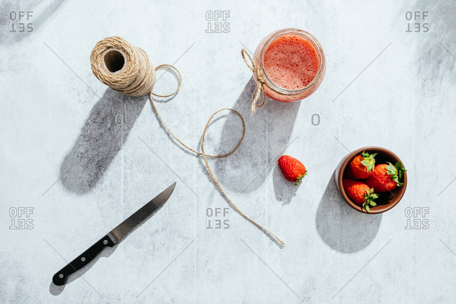 From above composition with fresh homemade strawberry juice in glass jar wrapped with twine placed on marble surface with whole berries and knife