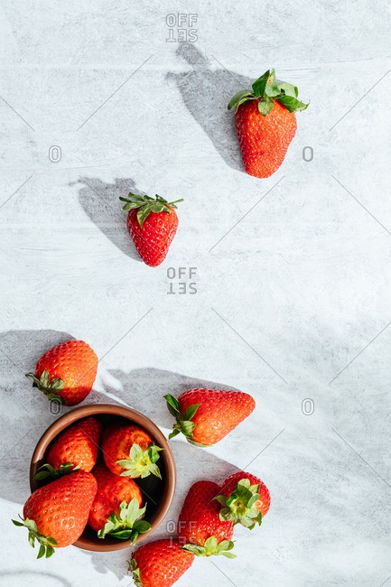 Top view composition with fresh ripe red strawberries placed in bowl and gray table under sunlight