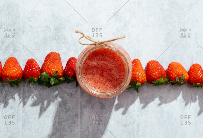 Composition with fresh homemade strawberry juice in glass jar wrapped with twine placed on marble surface with whole berries