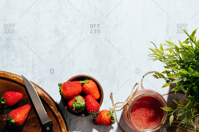 Composition with fresh homemade strawberry juice in glass jar wrapped with twine placed on marble surface with whole berries and knife