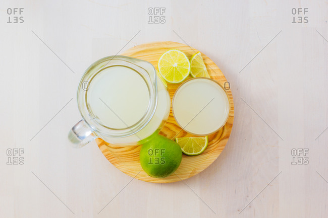 From above top view of homemade refreshing lemonade in server in glasses on wooden tray in white table background