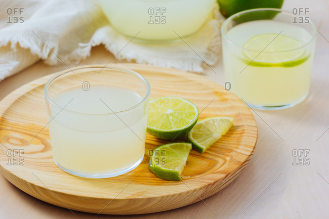 From above homemade refreshing lemonade in server in glasses on wooden tray in white table background