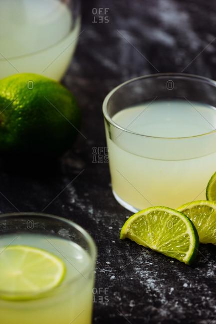 From above homemade refreshing lemonade in server in glasses on black marble background