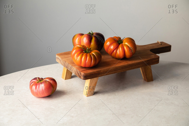 From above composition with raw red tomatoes arranged on wooden board on marble table