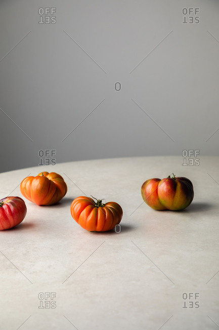 Ripening tomatoes on white table