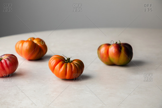 From above of appetizing red organic tomatoes prepared for cooking placed on round table in kitchen