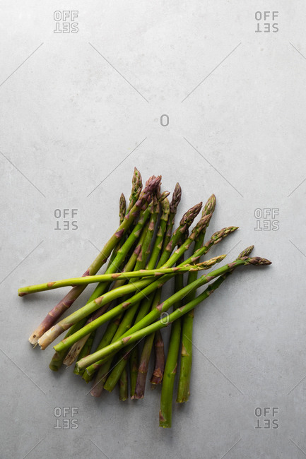 Top view of bunch of fresh green asparagus prepared for healthy vegetarian salad placed on marble table