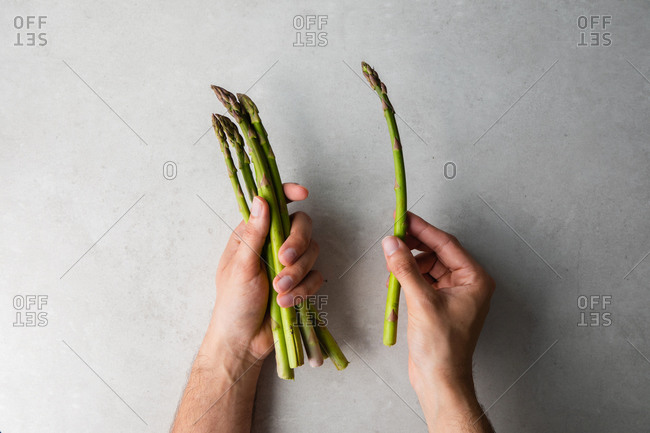 Cook holding bunch of fresh asparagus
