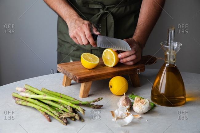 Crop anonymous male chef slicing fresh lemon on wooden board while preparing healthy dish at table with ingredients for recipe