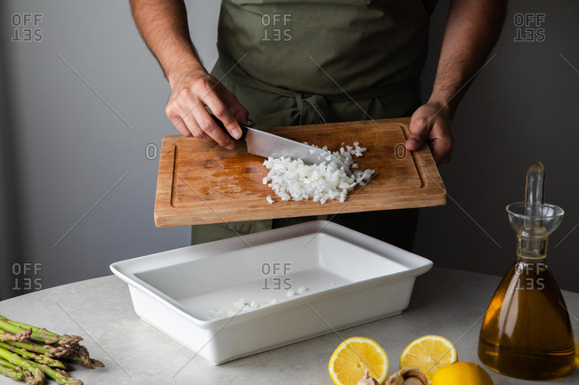 Cook putting cut onion into tray