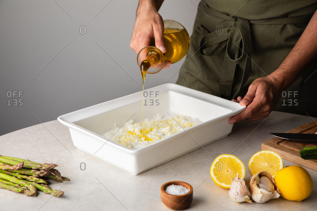 Crop anonymous cook pouring olive oil into baking tray with chopped onion while preparing dinner at kitchen table