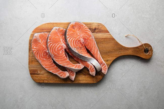 Top view of fresh salmon steaks on wooden board prepared for delicious healthy recipe placed on marble table