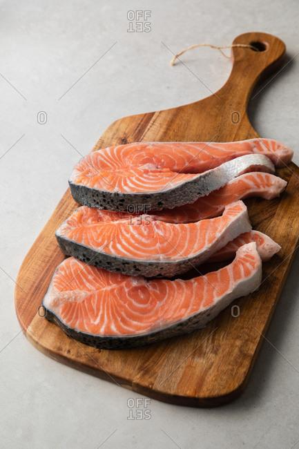 Fresh fish steaks on wooden board