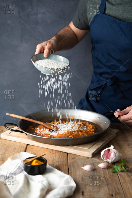 Crop man in dark blue apron adding white rice to chopped roasted ingredients on big metal pan while preparing yummy savory dish at home