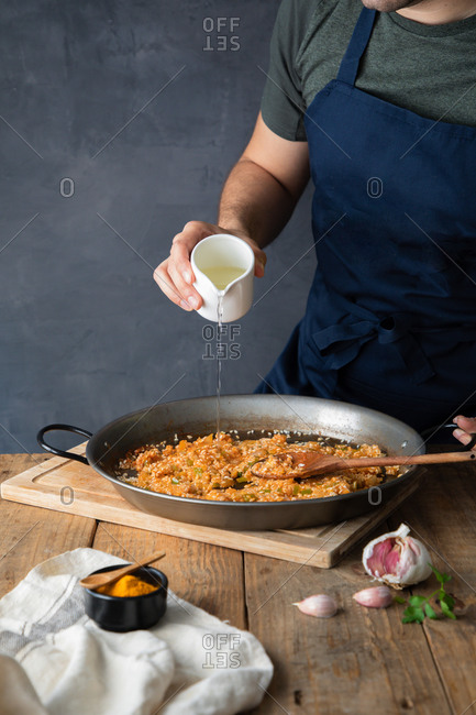 Crop man in dark blue apron pouring oil to rice with chopped roasted ingredients on large metal pan while cooking appetizing savory dish at home