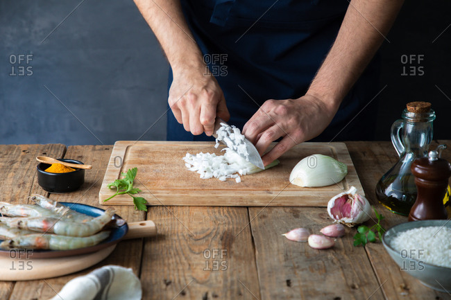 From above faceless chef cutting onion on cutting board while preparing appetizing dish at wooden table with bowl of rice and raw shrimps in composition with other ingredients at home