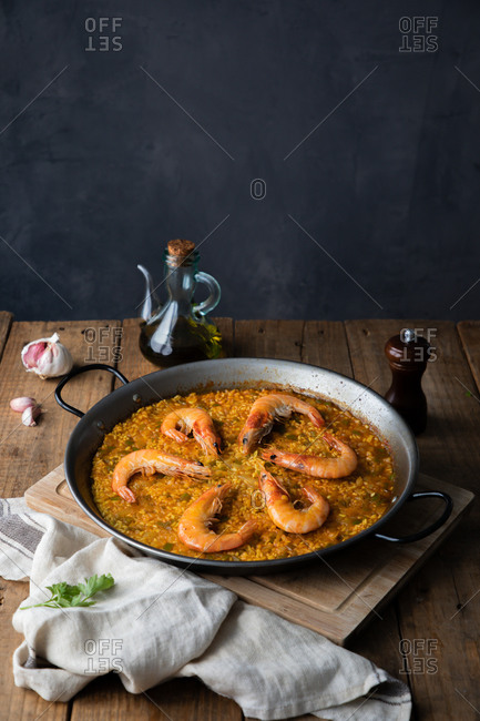 High angle of big metal pan of while appetizing paella with roasted shrimps on rustic table in composition with vintage bottle of oil and towel in kitchen at home