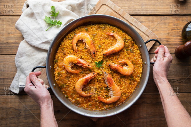 From above crop chef holding large metal pan of while appetizing nutrient paella with roasted shrimps against rustic table in kitchen at home