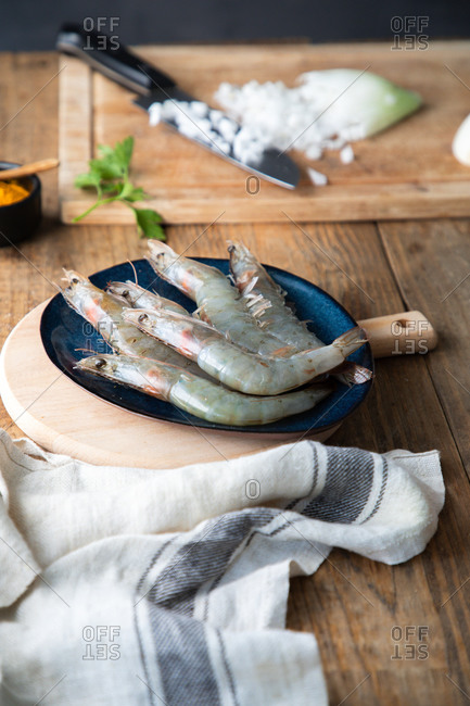 High angle of big raw gray shrimps on big blue plate on cutting board on rustic wooden table in light kitchen