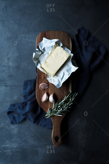 Top view of opened pack of butter in composition with cloves of garlic and rosemary stems on wooden cutting board and textile placed on dark table in kitchen in rustic style
