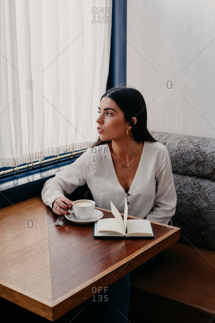 Brunette woman with long hair drinking coffee in a bar with a book next to it