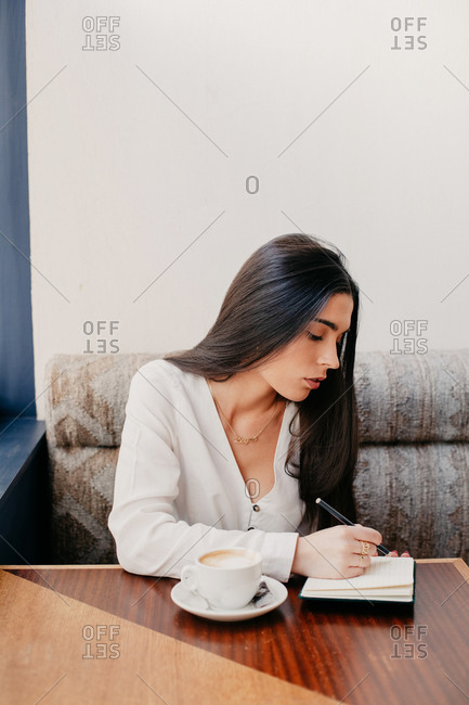 Brunette woman writing in a notebook in a bar