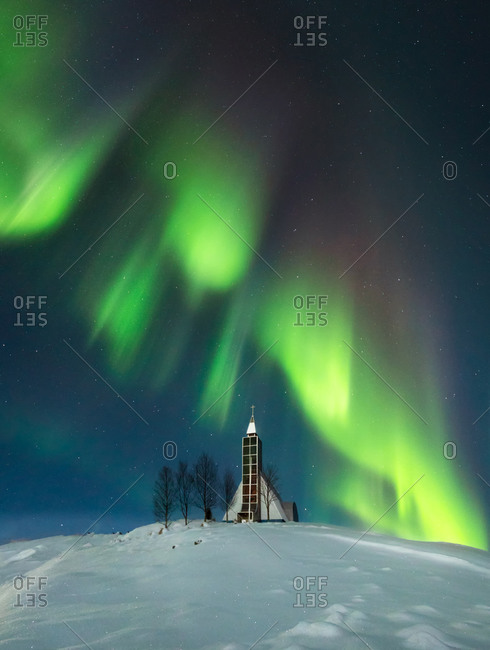 Amazing scenery of glowing colorful Northern lights in dark sky over snowy terrain with small village church and trees in Iceland
