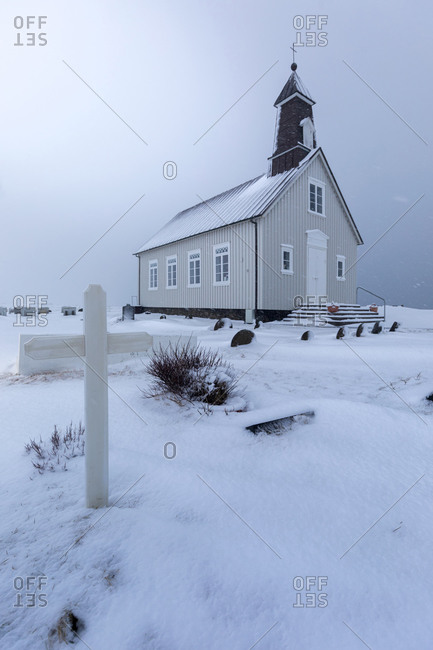 Low angle of small village church located near local cemetery with white cross among snowy field against gray overcast sky in winter day in Iceland
