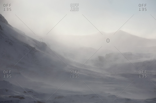 Snow covered volcano in foggy mountainous terrain