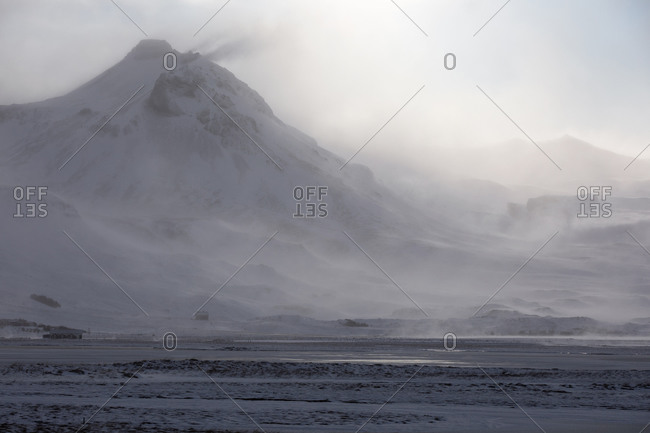 Severe wild landscape of snow capped volcano and mountain range during blizzard in winter day in Iceland