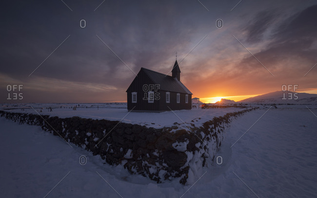 Amazing Northern scenery with small church located on desert snowy terrain against overcast evening sky during sunset in Iceland