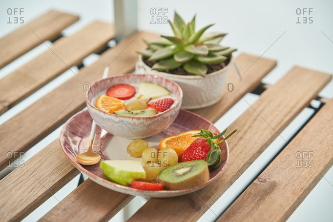 From above of tasty healthy breakfast with yogurt and assorted colorful fresh fruits served on wooden table