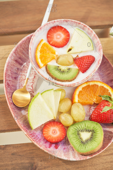 From above top view of tasty healthy breakfast with yogurt and assorted colorful fresh fruits served on wooden table