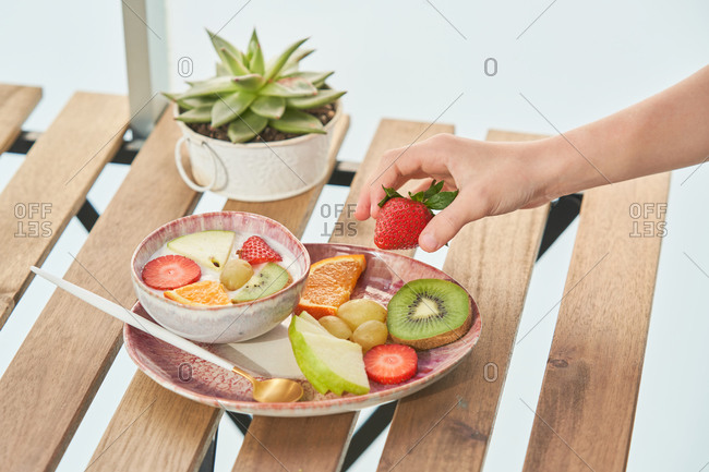 From above of crop unrecognizable female hands having healthy breakfast and eating delicious yogurt with sliced fresh assorted fruits served on wooden table