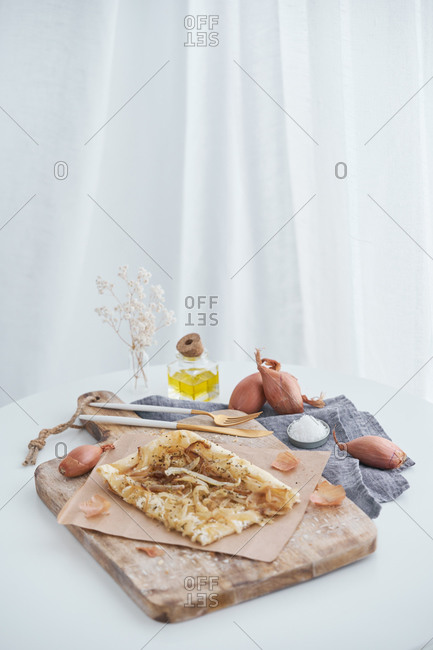 From above delectable puff pastry with onion and cream cheese placed on rustic cutting board on table near cooking ingredient at home