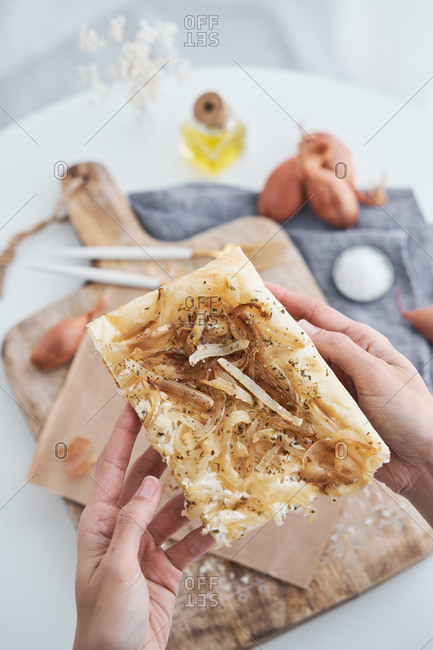 From above anonymous person taking slice of delicious puff pastry with onion and cream cheese from rustic wooden cutting board near utensils and cooking ingredients