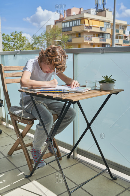Focused boy with curly hair sitting at table and drawing while resting on balcony on sunny summer day