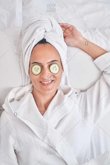 Top view of positive young female in white bathrobe and towel with cucumber slices on eyes enjoying natural beauty treatment at home