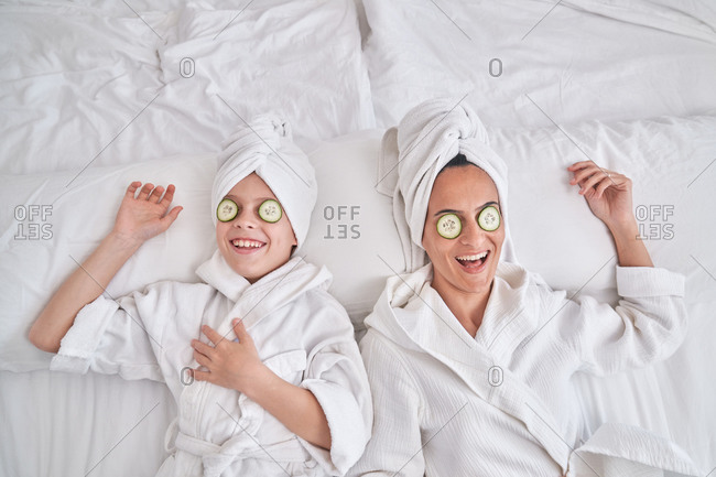From above of happy young female and kid wearing white bathrobes and towel turbans lying on bed with cucumber slices on eyes and laughing while having fun and enjoying beauty procedure at home